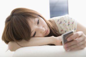 寝ころびスマホを見る女性