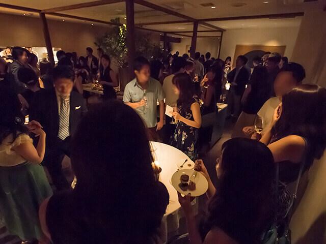 東カレ会員内同士のパーティーにて多くの男女が立食で語り合っているの実際の現場写真