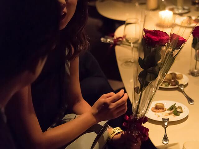 東カレ会員内同士のパーティーにて女性がバラを受け取りウマが合った者どうしが着席して語り合う実際の現場写真