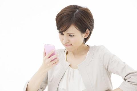 スマホの自撮り写真を見て悩む女性