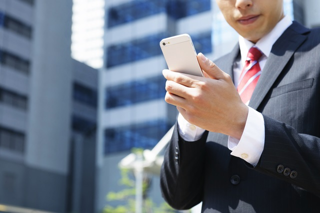 スマートフォンを見るアラサー男性