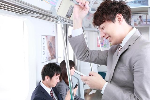 電車でスマホをいじる男性